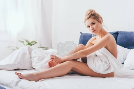 Photo pour Belle femme blonde assise au lit le matin - image libre de droit