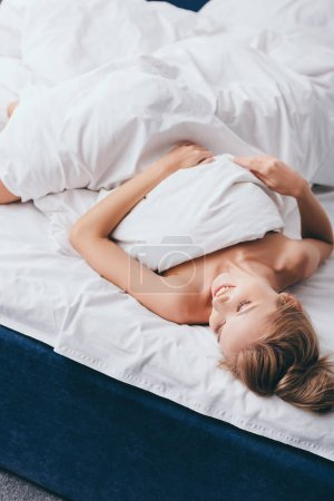 Photo for Beautiful smiling woman lying in bed in morning - Royalty Free Image