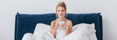 Photo pour Plan panoramique de femme heureuse attrayante avec tasse de café assis dans le lit le matin - image libre de droit