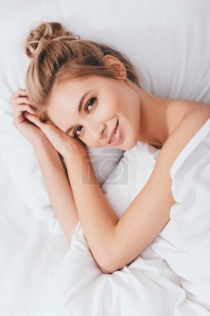 Photo for Attractive smiling woman lying in bed in morning - Royalty Free Image