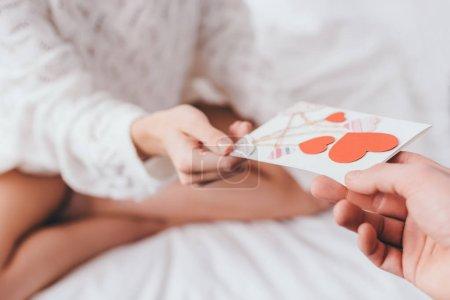 Photo pour Crochet vue de la femme prenant la carte de voeux avec des coeurs pour valentins jour de l'homme au lit - image libre de droit