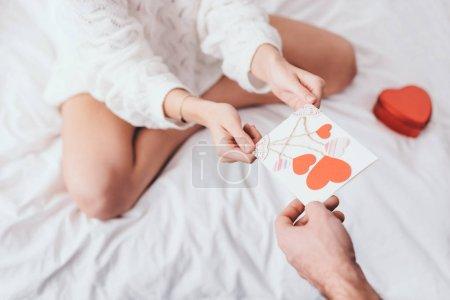 Photo pour Vue de la femme prenant la carte de voeux avec les cœurs pour valentins jour de l'homme au lit avec boîte cadeau - image libre de droit