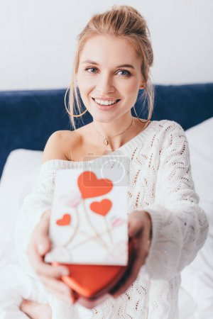 Photo pour Focus sélectif de la femme heureuse tenant une boîte-cadeau et une carte de la Saint-Valentin sur le lit - image libre de droit