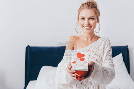 Photo for Beautiful smiling woman holding gift box and valentine card on bed - Royalty Free Image
