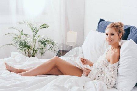 Photo pour Une femme souriante faisant des achats en ligne avec carte de crédit et tablette numérique au lit - image libre de droit
