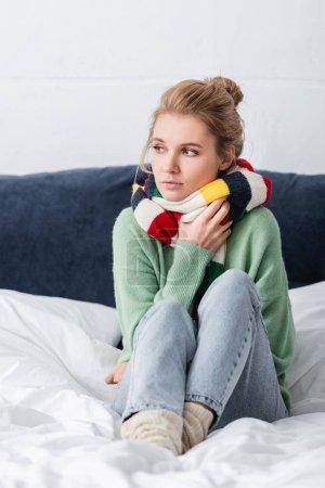 Photo pour Jeune femme malade en pull et écharpe assis sur le lit - image libre de droit