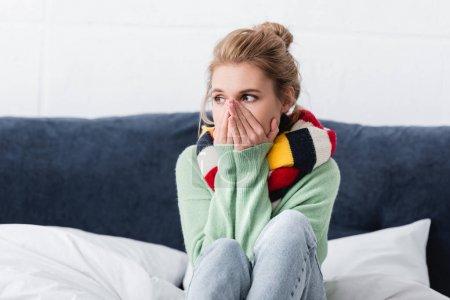 Foto de Joven enferma en jersey y bufanda sentada en la cama - Imagen libre de derechos