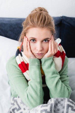 Foto de Triste mujer enferma en jersey y bufanda de pañuelos en la cama - Imagen libre de derechos