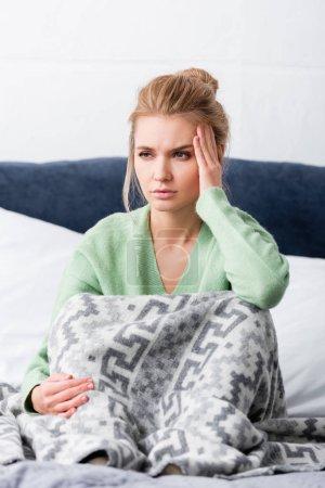 Photo pour Femme fatiguée ayant mal à la tête et assise sur le lit - image libre de droit