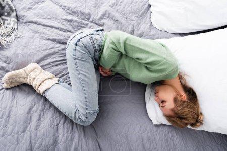 Photo pour Vue de dessus de la femme ayant des douleurs abdominales et couché sur le lit - image libre de droit