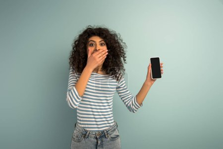 Foto de Shock bi-racial girl covering mouth with hand while showing smartphone with blank screen on grey background. - Imagen libre de derechos