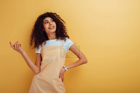 happy bi-racial girl looking away while standing with hand on hip on yellow background