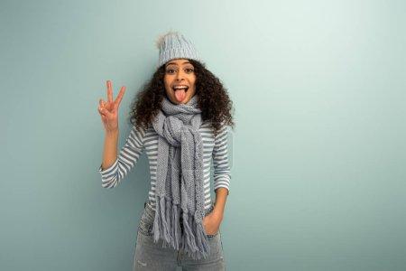 Photo pour Joyeuse fille bi-raciale en chapeau chaud et écharpe sortant de la langue et montrant un geste de victoire sur fond gris - image libre de droit