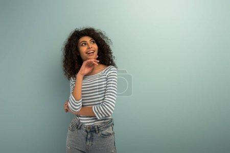 glückliches zweirassiges Mädchen lächelt, während es auf grauem Hintergrund wegschaut