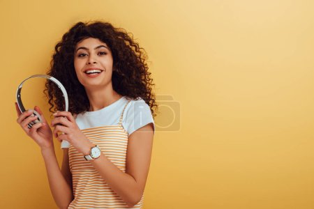 happy bi-racial girl smiling at camera while holding wireless headphones on yellow background