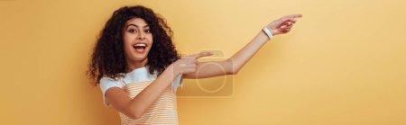 Photo for Panoramic shot of cheerful bi-racial girl pointing with fingers on yellow background - Royalty Free Image