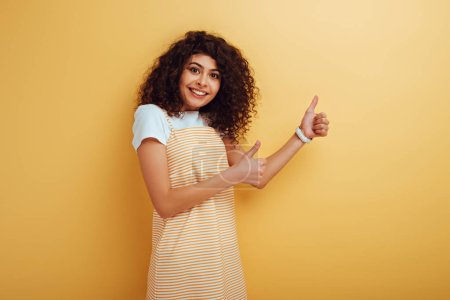 Photo for Cheerful mixed-race girl showing thumbs up while looking at camera on yellow background - Royalty Free Image