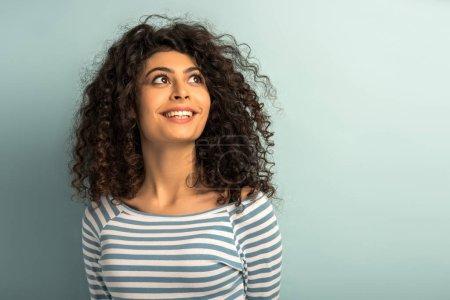 attraktives, fröhliches Mischlingsmädchen, das vor grauem Hintergrund wegsieht und lächelt