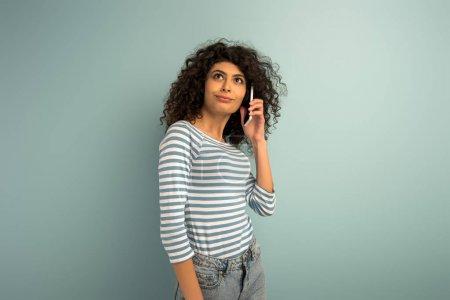 Foto de Carrera mixta escéptica mirando hacia otro lado mientras habla en el teléfono inteligente sobre fondo gris - Imagen libre de derechos