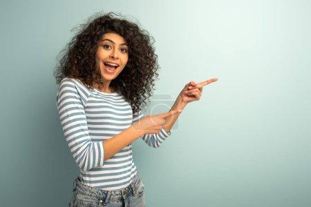 Photo pour Excité mixte race fille regardant caméra tout en pointant avec les doigts sur fond gris - image libre de droit