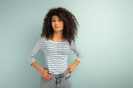 Photo for Skeptical mixed girl looking at camera while holding hands on hips on grey background - Royalty Free Image