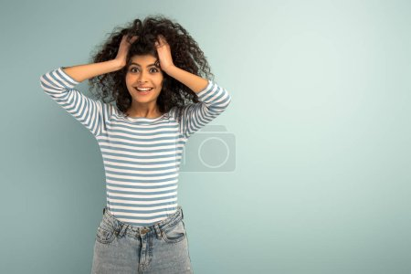 Excited mixed race girl touching hair while looking at camera on grey background