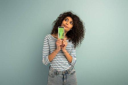 Photo pour Une jeune fille métisse réfléchie regarde ailleurs en montrant un smartphone avec la meilleure application de magasinage sur fond gris - image libre de droit