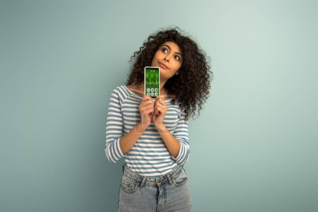 Photo for Thoughtful mixed race girl looking away while showing smartphone with fitness tracker app on grey background - Royalty Free Image