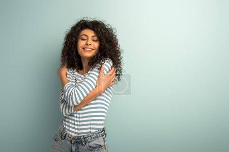 glücklich gemischtes Rassenmädchen umarmt sich im Stehen mit geschlossenen Augen auf grauem Hintergrund