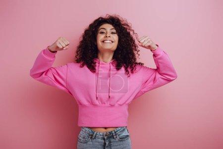 Photo pour Une jeune fille biraciale excitée fait un geste de vainqueur tout en souriant à la caméra sur fond rose - image libre de droit