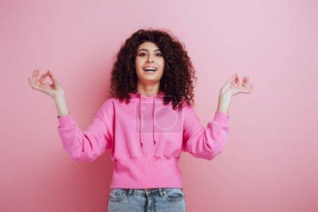 Photo pour Une joyeuse fille bi-raciale regardant la caméra alors qu'elle se tient debout en méditation pose sur fond rose - image libre de droit