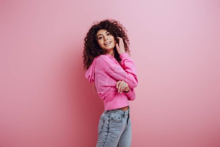 Photo for Flirty, smiling bi-racial girl touching hair while smiling at camera on pink background - Royalty Free Image
