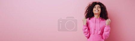 Photo pour Photo panoramique d'une jeune fille biraciale excitée montrant un geste de vainqueur debout les yeux fermés sur fond rose - image libre de droit