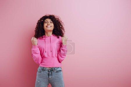Photo pour Excitée bi-raciale fille montrant le geste gagnant tout en se tenant les yeux fermés sur fond rose - image libre de droit