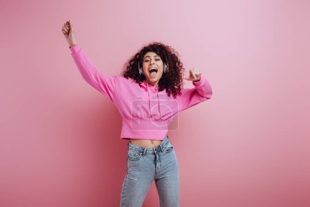 Photo for Excited mixed race girl dancing and singing while listening music in wireless headphones on pink background - Royalty Free Image