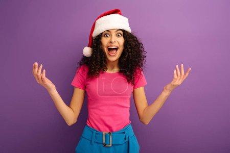 Photo for Amazed bi-racial girl in santa hat looking at camera while standing with open arms on purple background - Royalty Free Image
