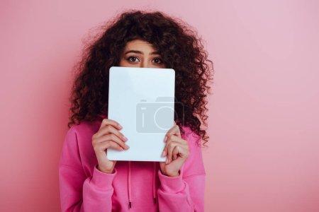 Photo pour Jeune femme bi-raciale regardant la caméra tout en obscurcissant le visage avec tablette numérique sur fond rose - image libre de droit