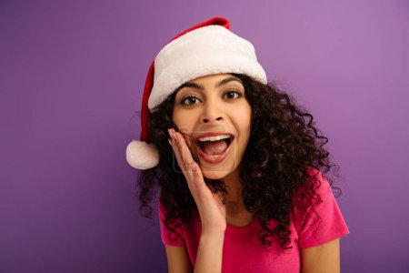 Photo for Excited bi-racial girl in santa hat screaming at camera on purple background - Royalty Free Image