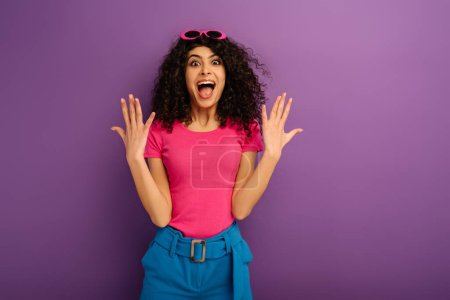 Photo for Excited bi-racial girl showing wow gesture while looking at camera on purple background - Royalty Free Image