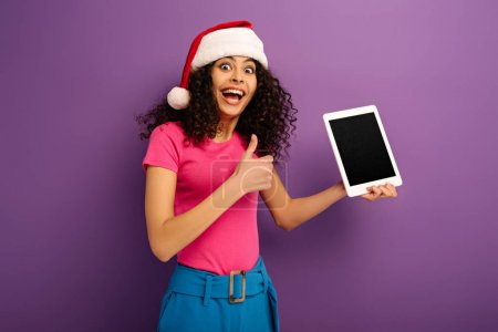 Photo for Excited bi-racial girl in santa hat showing thumb up while holding digital tablet with blank screen on purple background - Royalty Free Image