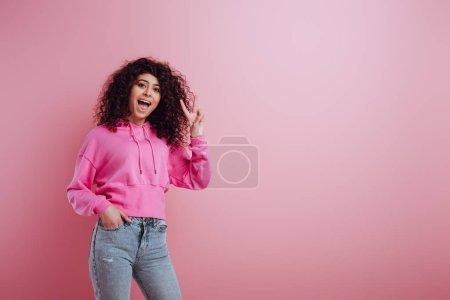 Photo pour Une joyeuse fille bi-raciale montrant un geste de victoire en tenant la main dans la poche sur fond rose - image libre de droit