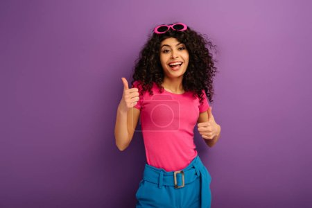Photo for Cheerful bi-racial girl showing thumbs up while smiling at camera on purple background - Royalty Free Image