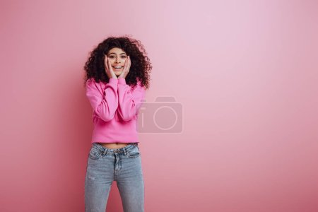 Photo for Happy bi-racial girl smiling at camera while touching face on pink background - Royalty Free Image