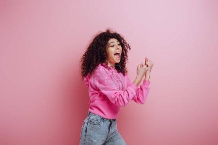 Photo pour Une jeune fille biraciale excitée criant tout en montrant un geste de vainqueur sur fond rose - image libre de droit