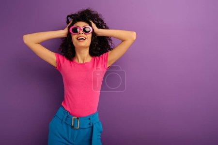 Photo pour Heureux bi-racial fille en lunettes de soleil toucher la tête et sourire sur fond violet - image libre de droit