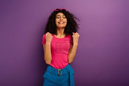 Photo pour Une jeune fille biraciale enthousiaste en train de faire un geste de vainqueur, les yeux fermés sur fond violet - image libre de droit