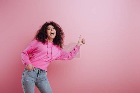 Photo pour Heureux bi-racial fille montrant pouce vers le haut tout en tenant la main dans la poche sur fond rose - image libre de droit