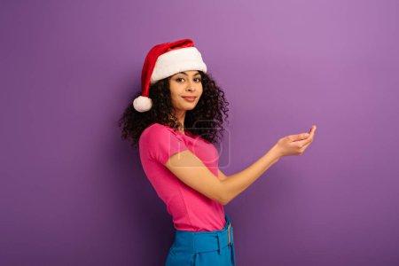 Photo pour Belle fille bi-raciale en santa chapeau souriant à la caméra tout en se tenant avec les mains tendues sur fond violet - image libre de droit