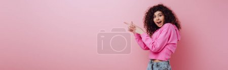 Photo for Panoramic shot of shocked bi-racial girl looking at camera while pointing with fingers on pink background - Royalty Free Image