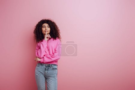 Photo pour Positive bi-racial girl looking away while showing hush gesture on pink background - image libre de droit